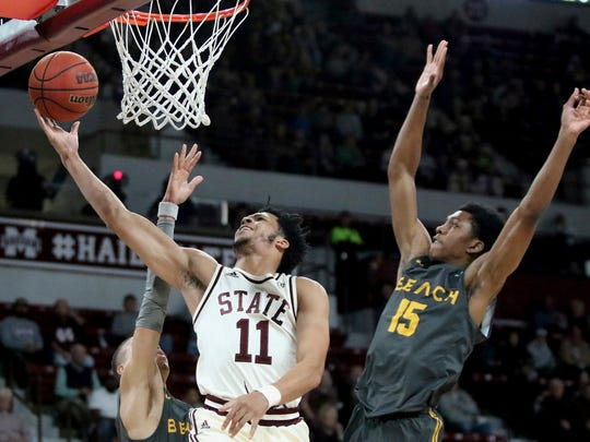 Mississippi State guard Quinndary Weatherspoon (11) drives to the basket between Long Beach State guards Ron Freeman and Deishuan Booker (15) during the first half of an NCAA college basketball game Friday, Nov. 16, 2018, in Starkville, Miss. (AP Photo/Jim Lytle)