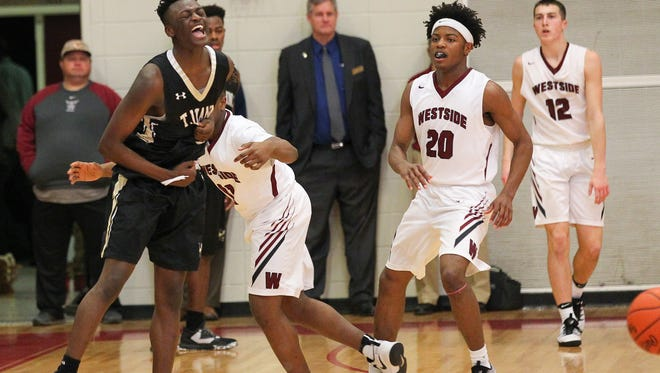 T.L. Hanna senior guard Tariq Thomas, left, reacts near Westside junior Kobe Middleton, middle, and Westside senior Ty Cobb, right, as time expires during the fourth quarter on Friday at Westside High School in Anderson. T.L. Hanna won 73-60.
