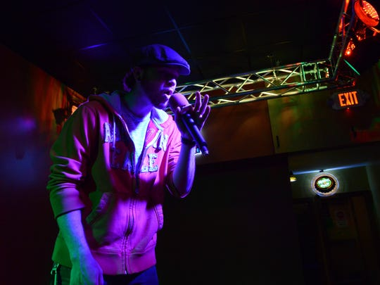 """Jacob Anderson, from Lancaster, sings The Neighbourhood's """"Sweater Weather"""" April 16 at the Orange Carpet in Lancaster. The downtown bar is one of many in the city that offers karaoke to customers."""