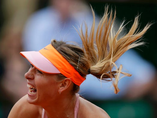 Maria Sharapova of Russia serves to Garbine Muguruza of Spain during their women's quarterfinal match at the French Open.