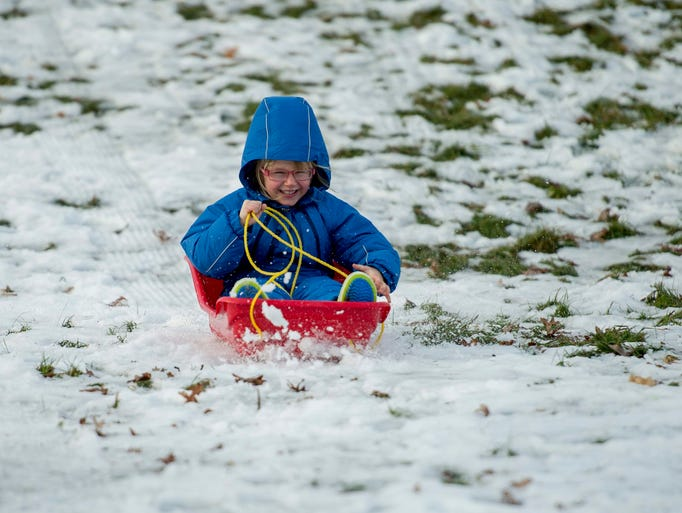Matilda Green, 4, rides a sled in the Arboretum on