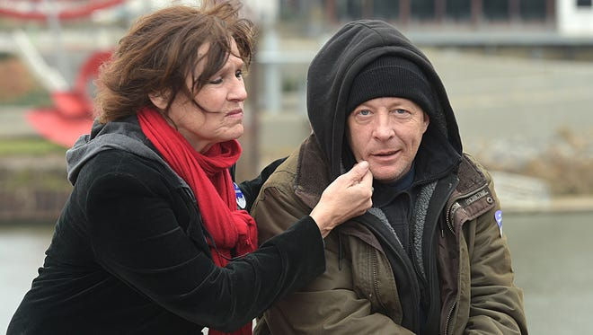 Sandy Griffin comforts David Watson, who has been homeless for six months, while attending the 2016 Annual Homeless Memorial to honor people who died from the homeless community this year. The event was held at Riverfront Park on Saturday, December 17, 2016.