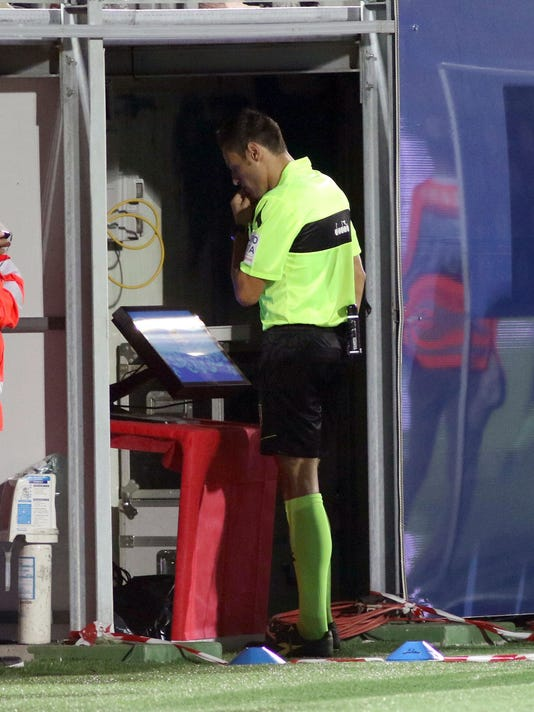 In this photo taken on Sunday, Aug. 20, 2017, referee Maurizio Mariani checks the VAR system before awarding a penalty kick during the Serie A soccer match between Crotone and AC Milan, at the Ezio Scida Stadium in Crotone, Italy.  The introduction of video review in Serie A was meant to eliminate controversial decisions. However, debate continues to rumble on after the first weekend using the new technology. (Albano Angilletta/ANSA via AP)