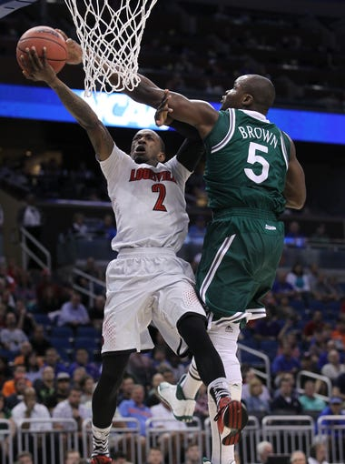 U of L's Russ Smith was fouled by Manhattan's Rhamel Brown, #5, during their NCAA game at the Amway Center in Orlando, Fl. Mar. 20, 2014