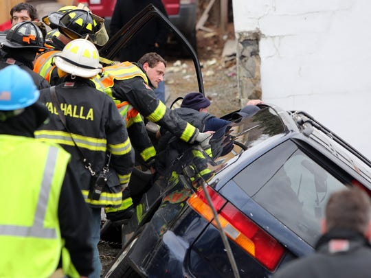 First responders remove a driver from a minivan that