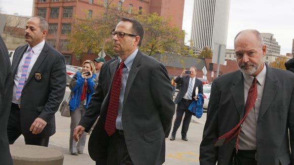 Navitech founder John Maggio, center in glasses, is escorted Nov. 6 from the Attorney General's office to the Rochester Police Dept. for booking as part of the LDC scandal investigation.