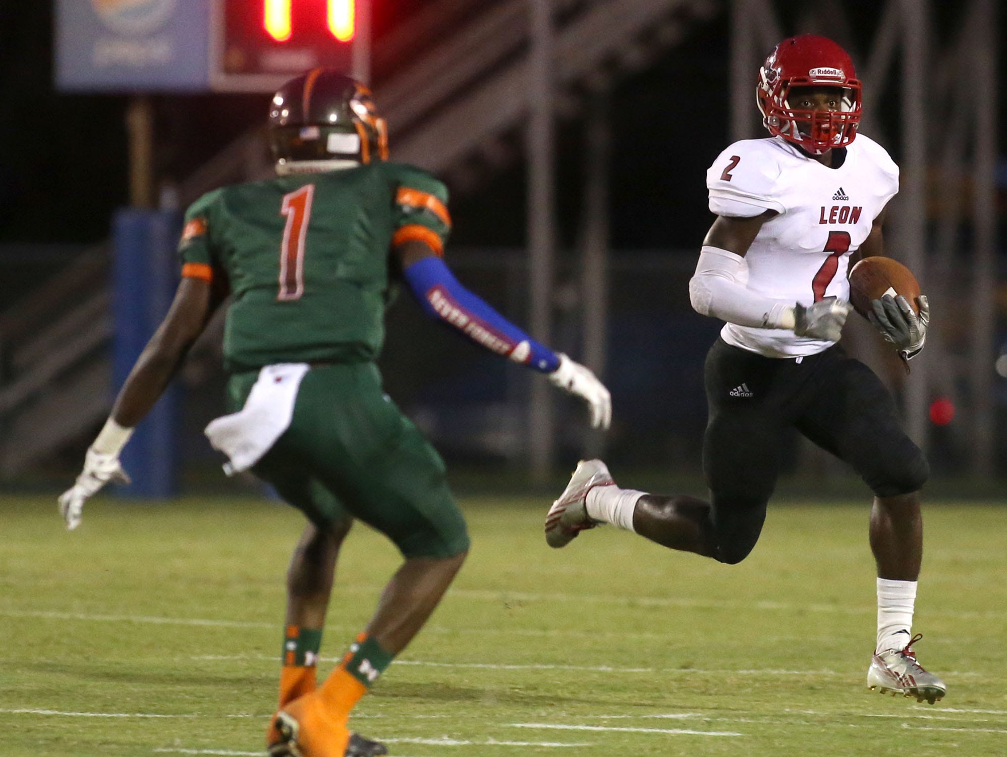 Leon's James Peterson runs the ball past Mosley's Devontia Wilson. Mosley faced off with Leon during a football game on Sept. 10. (Patti Blake | The News Herald)