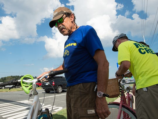 Mike Tyler with the Sussex Cyclists helps to install lights on bicycles during a bike safety check on Del. 1 in Rehoboth.