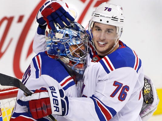New York Rangers goalie Henrik Lundqvist, left, of Sweden, celebrates with teammate Brady Skjei after the team's 3-1 win over the Calgary Flames in an NHL hockey game Friday, March 2, 2018, in Calgary, Alberta. (Larry MacDougal/The Canadian Press via AP)
