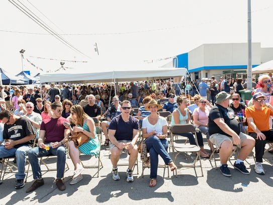 Attendees sit and drink beer while watching a band