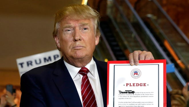 Donald Trump holds his GOP loyalty pledge during a news conference at Trump Tower in New York on Sept. 3, 2015.