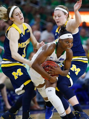 Florida Gulf Coast guard Kaneisha Atwater, center, splits the defense of Michigan guards Katelynn Flaherty, left, and Nicole Munger during the second half of U-M's loss in the WNIT semifinal Thursday in Fort Myers, Fla.