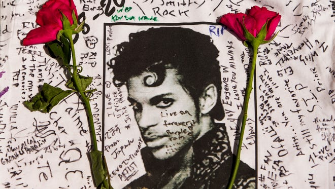 Flowers on a T-shirt signed by fans of Prince at makeshift memorial outside Apollo Theater in New York.