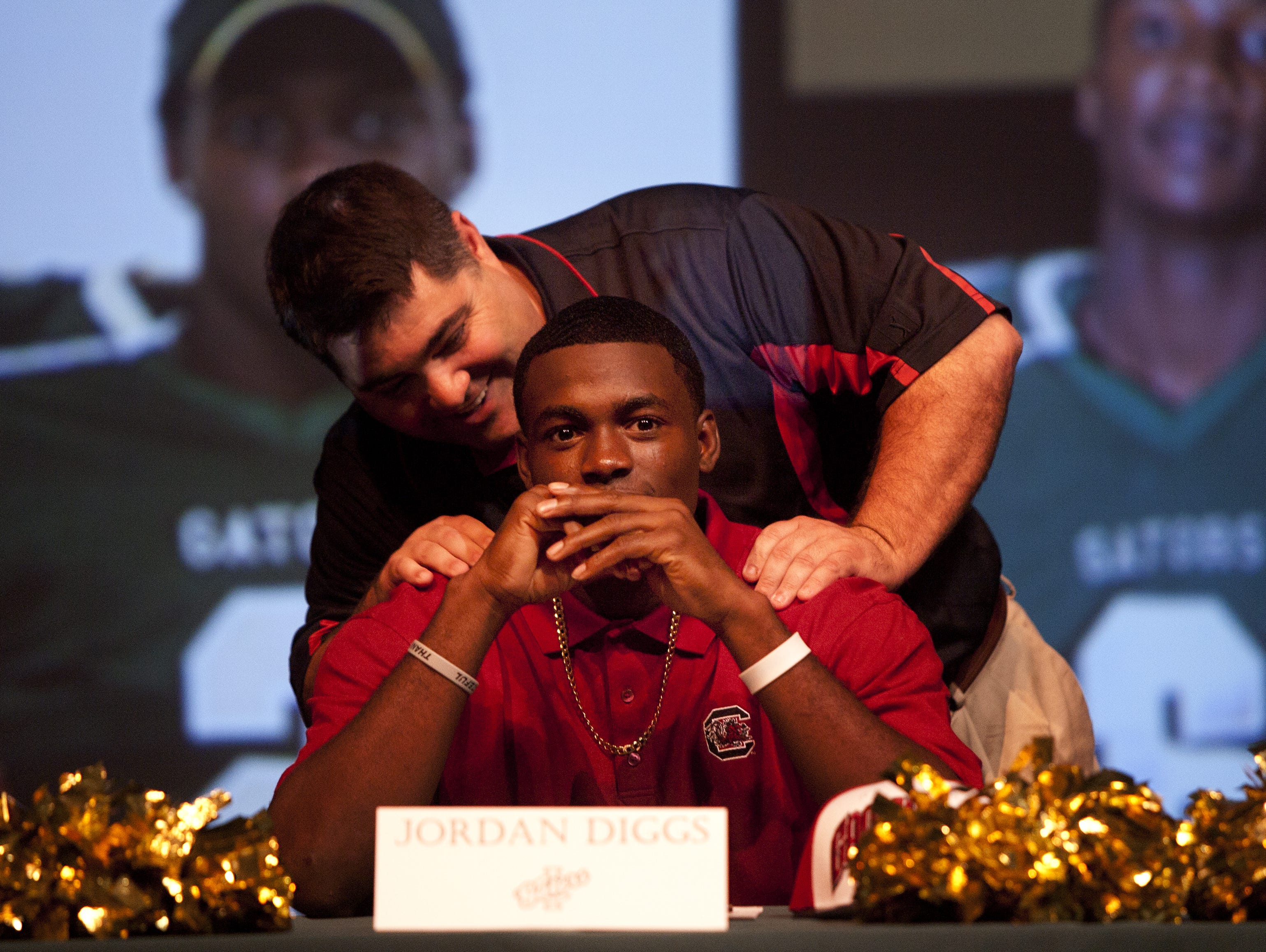 Island Coast High School football coach Joe Bowen speaks with Jordan Diggs before the start of the National Signing Day Ceremony at the school on Wednesday 2/1/2012. Diggs, who has experinced a huge amount of adveristy in his life, including watching his mother's boyfriend gunned down by an intruder in their house 6 days ago. He signed with South Carolina.