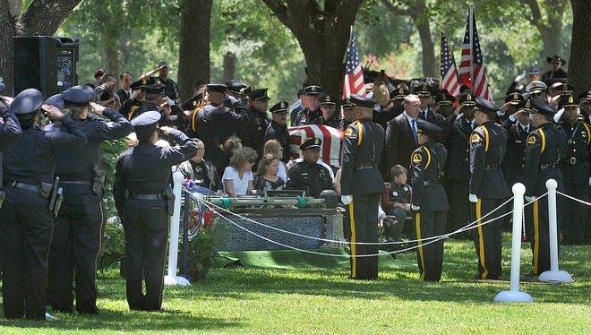 The casket of Dallas Police Sr. Cpl. Lorne Ahrens is carried to the grave site at Restland Memorial Park in Dallas on July 13, 2016.