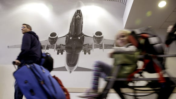 Travelers pass a large photograph of an airplane at