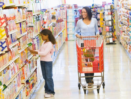 A woman pushing a shopping cart while a little girl shops