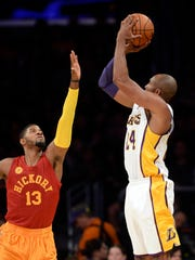Nov 29, 2015; Los Angeles, CA, USA; Los Angeles Lakers forward Kobe Bryant (24) shoots over Indiana Pacers forward Paul George (13) in the first half at Staples Center. Mandatory Credit: Richard Mackson-USA TODAY Sports