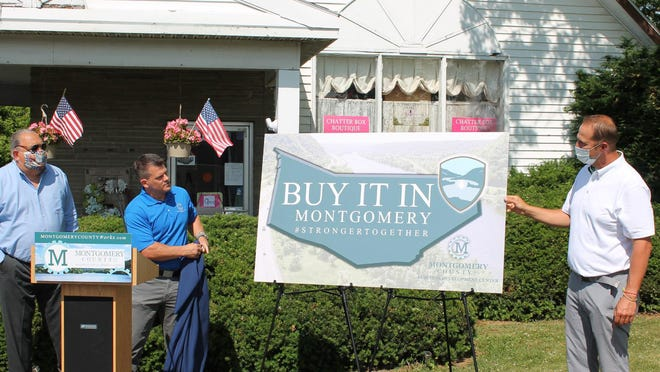"""Montgomery County Executive Matt Ossenfort, right, and Montgomery County Business Development Center Chief Executive Officer Ken Rose unveil the """"Buy It In Montgomery"""" logo, encouraging residents to shop local and support the county's small business community."""