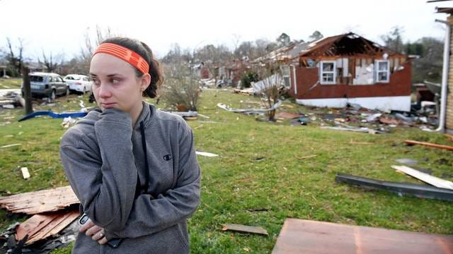 Meg Selby surveys the damage to her neighborhood after a tornado touched down Tuesday in Nashville.