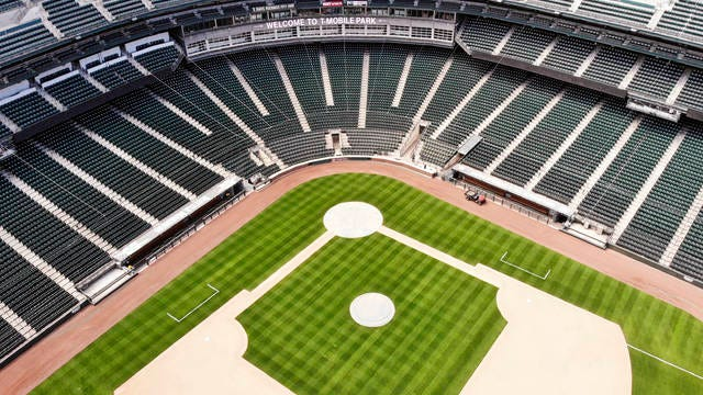 In an otherwise empty ballpark, grounds crew members continue to keep the Seattle Mariners' field in playing shape on May 11 in Seattle.