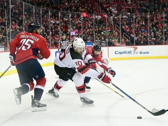 Apr 7, 2018; Washington, DC, USA; New Jersey Devils right wing Jimmy Hayes (10) reaches for the puck as Washington Capitals defenseman Michal Kempny (6) defends during second period at Capital One Arena.