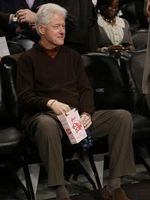 Bill Clinton snacks on popcorn at the Oklahoma City Thunder - Brooklyn Nets game Jan. 31 in New York.