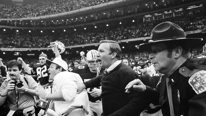 FILE - In this Jan. 3, 1984, file photo, Auburn head coach Pat Dye, center, rushes onto the field after his team beat Michigan 9-7 in the Sugar Bowl at the Superdome in New Orleans. Former Auburn coach Pat Dye, who took over a downtrodden football program in 1981 and turned it into a Southeastern Conference power, has died. He was 80. Lee County Coroner Bill Harris said Dye passed away Monday, June 1, 2020, at the Compassus Bethany House in Auburn, Ala.
