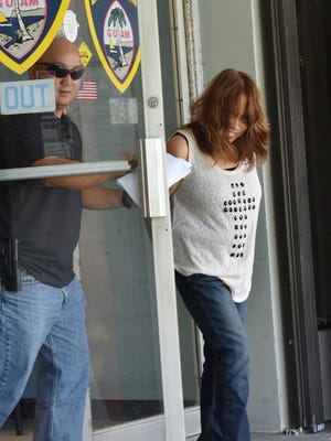 In this file photo, Frances Marie Manglona Quinata is escorted out of the Guam Police Department Hagåtña precinct.