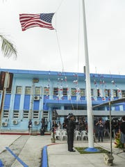 Police officers of the Port Authority of Guam hoist an American flag during the singing of the national anthem in Piti on Monday, Oct. 19. The agency is celebrating Port Week to commemorate 40 years of service to Guam and the region.