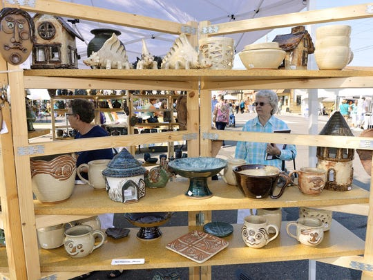 Terri Schrode, left, and Coletta Boeckmann, St. Cloud, admire some of the ceramics from Falling Leaf Pottery of St. Cloud at a past Millstream Arts Festival.