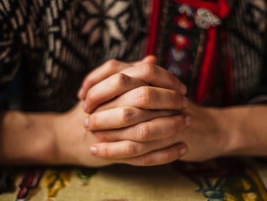 A woman's hands are folded for a prayer.