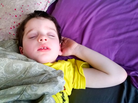 Candid pose of young child sleeping in bed