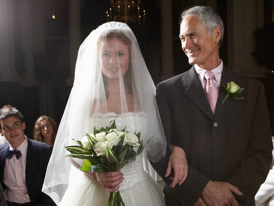 Bride walking down aisle, arm linked with father's, smiling