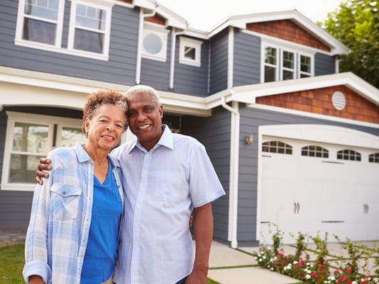 Senior black couple standing outside a large suburban house