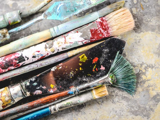Paint brushes and scraper with dried paint on them