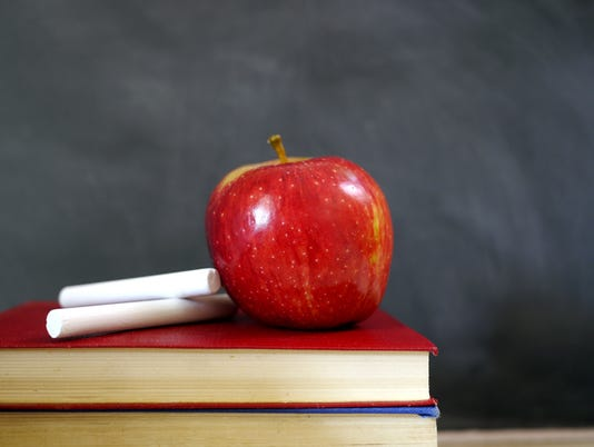 red apple and chalk on books