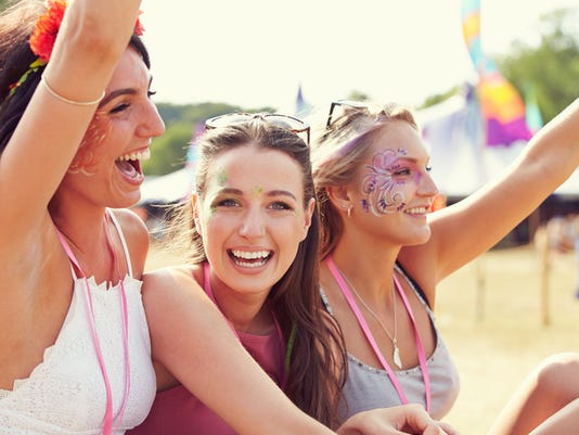 Three girl friends at music festival, one turned to camera