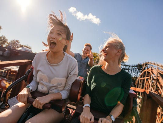 Young friends on thrilling roller coaster ride