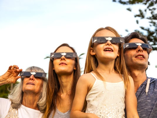 Family looking at Solar Eclipse using solar glasses