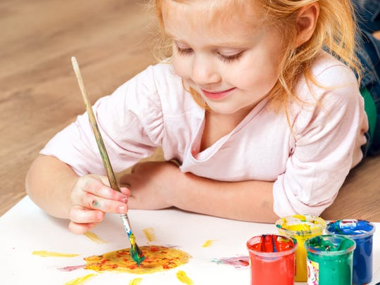Young girl painting with brush
