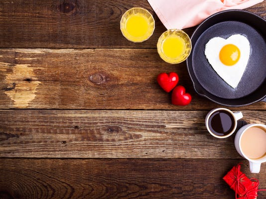 Valentines day table - heart shape fried egg, fresh orange juice and coffee