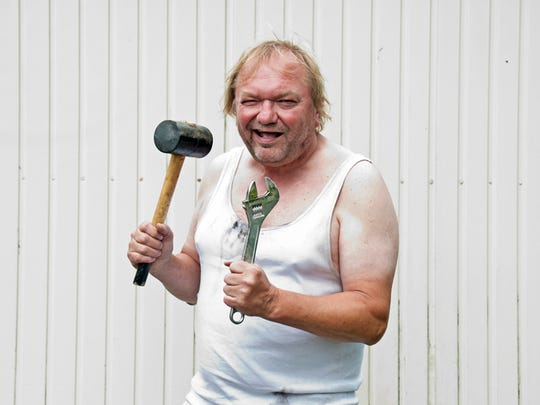 Man with rubber hammer and wrench, in front of a garage
