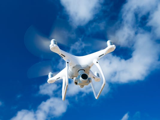 drone flying over sea. white drone hovering in a bright blue sky