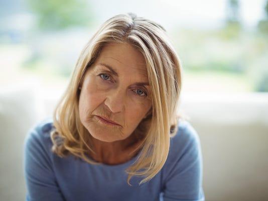 Portrait of sad senior woman sitting on bed