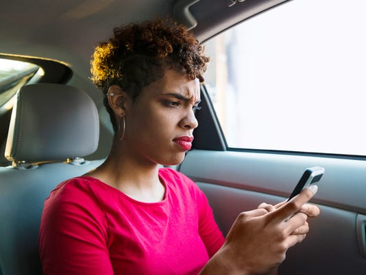 Annoyed Millennial Passenger Makes a Face while Texting in Backseat