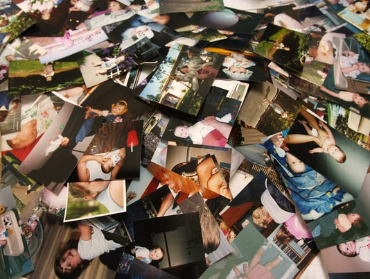 Unorganized pile of photographs of a little girl's life