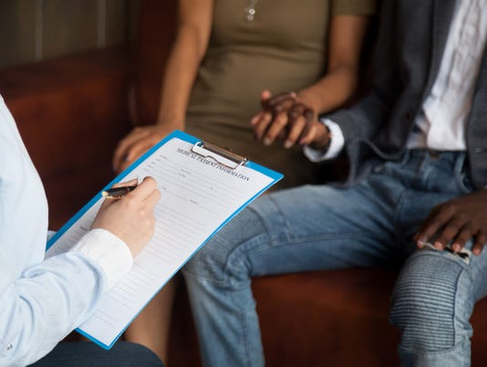 Psychologist filling medical patient information form consulting african couple, closeup