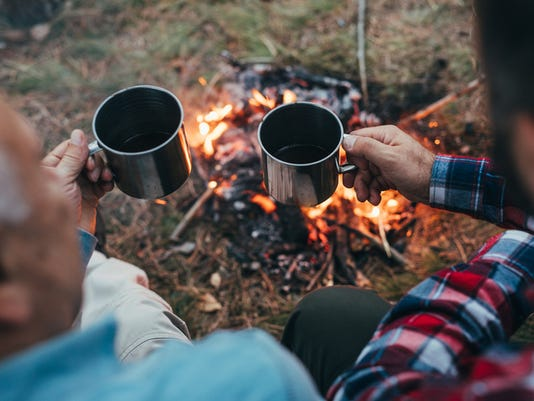 Drinking coffee near fire in nature