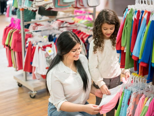 Mother and daughter shopping for clothes at a store
